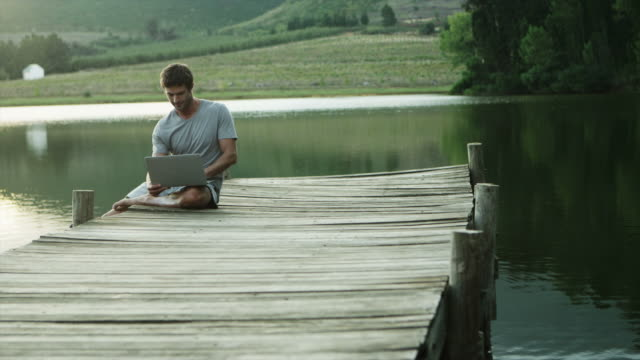 WS DS of man sitting on jetty by lake using laptop