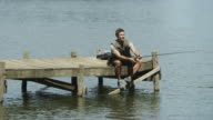 WS of man sitting on jetty fishing
