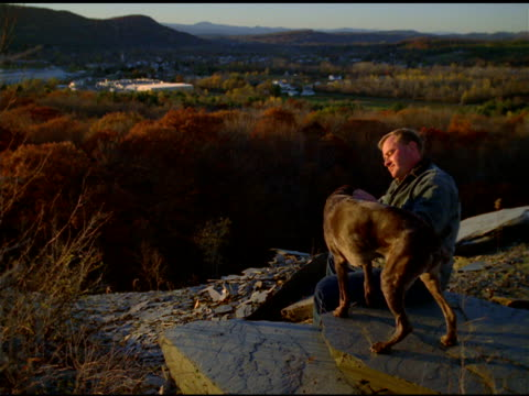 Man sitting on rock strokes pet Labrador dog, Granville, New York State