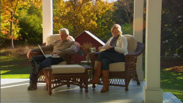 WS Man sitting on wicker chair on porch using laptop as woman sits next to him reading/ Livingston, New York