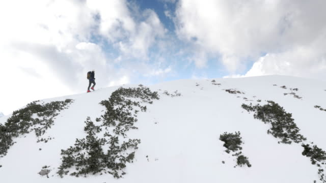 AERIAL Man ski touring on the mountain top