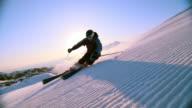 SLO MO Man skiing down slope with sun behind him