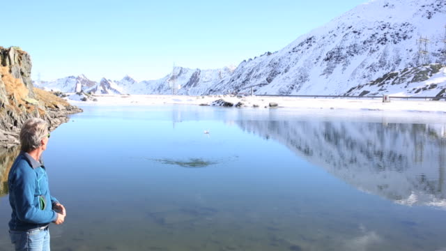 Man skips stone across mountain pond, under snowy mtns