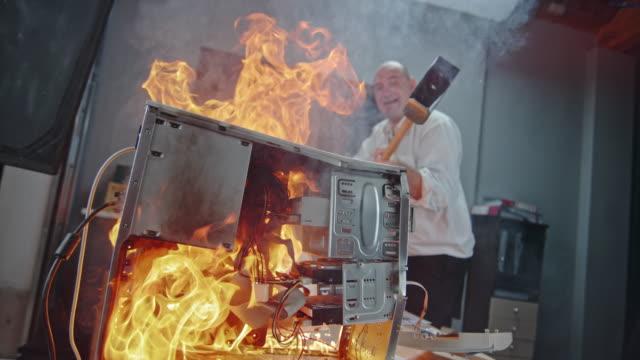 SLO MO Man slamming the burning computer with hammer