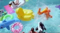 MS SLO MO Man sliding down water slide into pool filled with inflatable pool toys