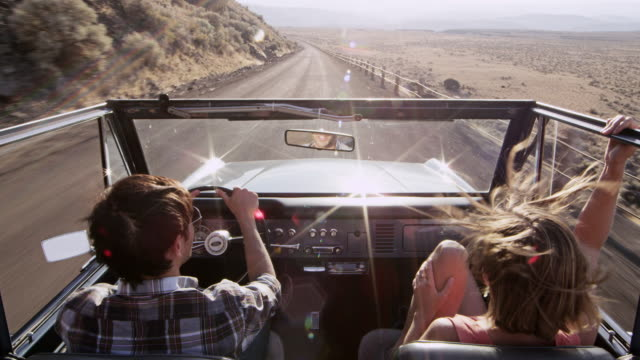 MS man smiling driving convertible off road vehicle on rural desert road woman riding in passenger seat