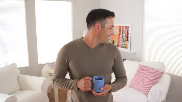 man smiling with mug of coffee in living room