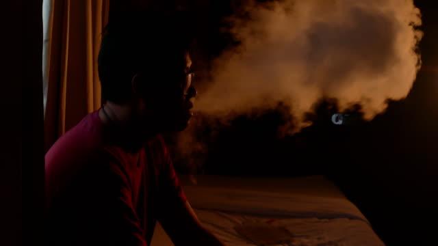 man smoking electric e cigarette vapor in dark room