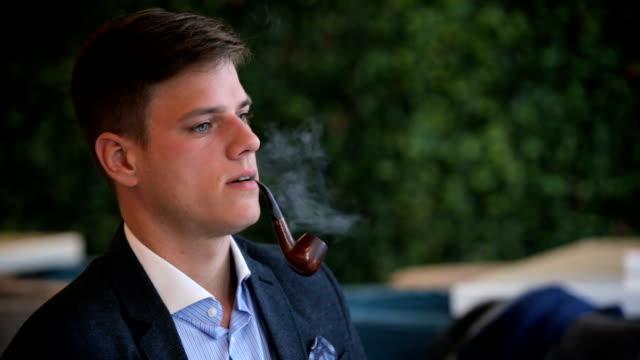 Man smoking pipe, drinking coffee