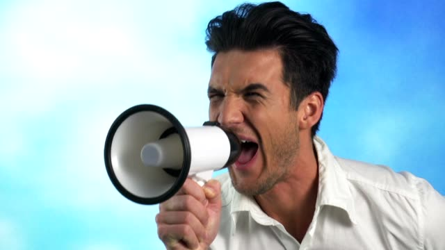 Man speaking into megaphone, drawing attention