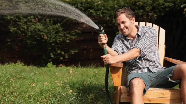 Man spraying hose from lawn chair
