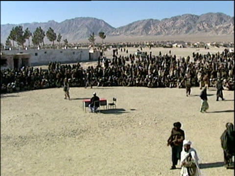 Man standing alone from crowd and imploring with official sat at table at refugee camp; Afghanistan Refugee Crisis 2001