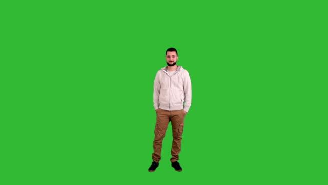 Mann steht und schaut in die Kamera auf einem grünen Hintergrund Leinwand