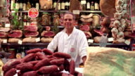 PORTRAIT Man standing behind counter in deli surrounded by meats + cheeses / Florence, Italy