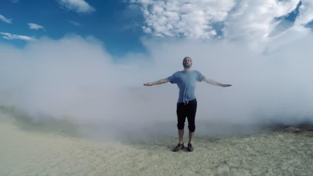 Mann steht in einem Dampf aus isländischer Geysir.