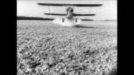 / man standing in front of line of crop dusters in a farm field / crop duster flies across field spraying for mosquitoes / cloud of chemicals fills...