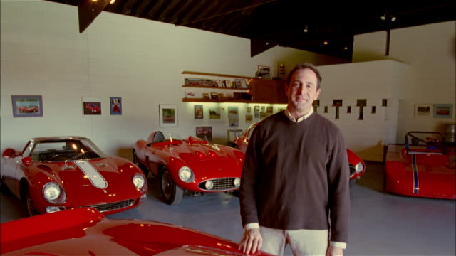 MS, man standing in garage amongst vintage cars, portrait, USA, Pennsylvania, Solebury