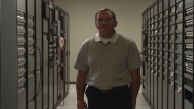 MS Man standing in server room corridor, Dallas, Texas, USA