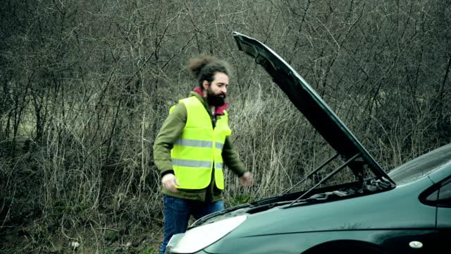 Man standing next to broken car