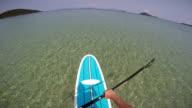 POV uomo in piedi su una paddle board in acque tropicali