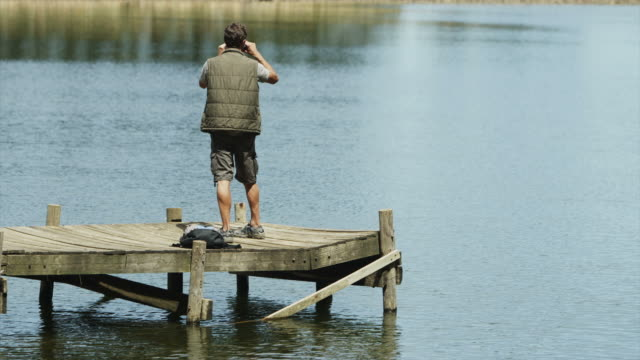 WS of man standing on jetty with binoculars turning in circle