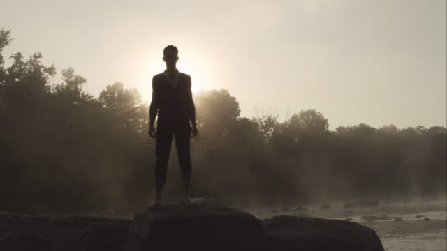 Man standing on large rock in river looking at camera at sunrise