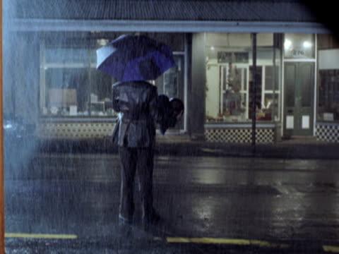 WS Man standing on street in rain, New Zealand
