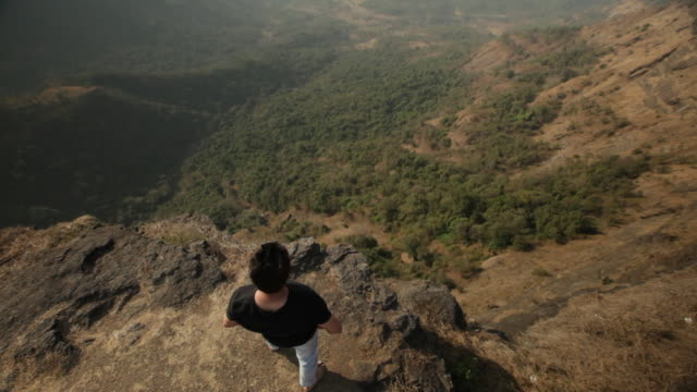 Man standing on the cliff of mountain