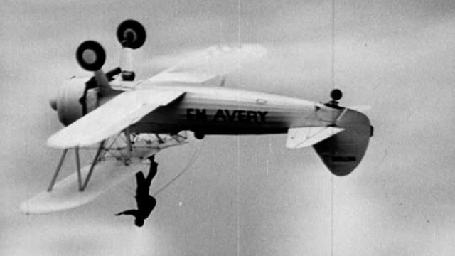 Man standing on top of biplane wings while airplane goes upside down / airplane says EM Avery on wing 1920s