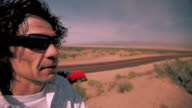 A man stands away from a highway and looks out over the desert.