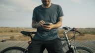 Man stands in a mountain bike while using a smartphone