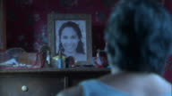 A man stares at a photograph of a beautiful young woman on his bedroom dresser.