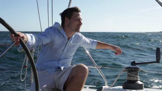 MS man steering yacht in sun and blue sea/Puerta Banus/Andalucia/Spain