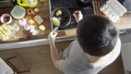 Man stirring fried eggs in modern kitchen