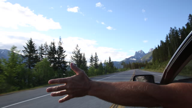 Man stretches arm out of car window, mountain road
