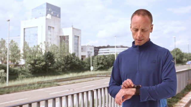LD Man stretching and checking his watch before jogging