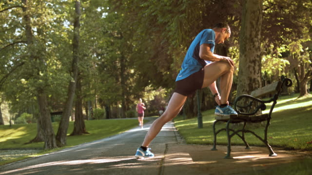 SLO MO DS Man stretching benen på en parkbänk