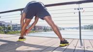 Man stretching on a bridge