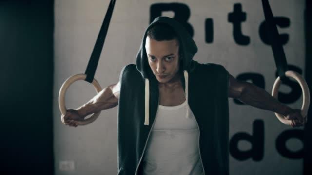 Mann stretching auf Gym Ringe