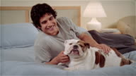 MS, Man stroking Bulldog on bed, portrait