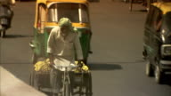 A man struggles to pedal his bicycle cart on the edge of the street.