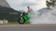 Man stunts with motorbike on mountain road