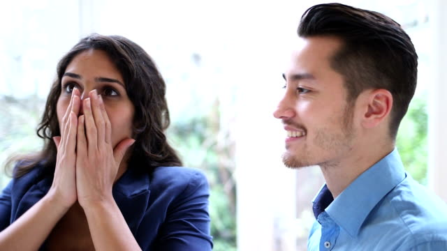 Man surprising young woman and kissing