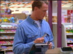 Man swiping card at checkout register in supermarket + signing receipt