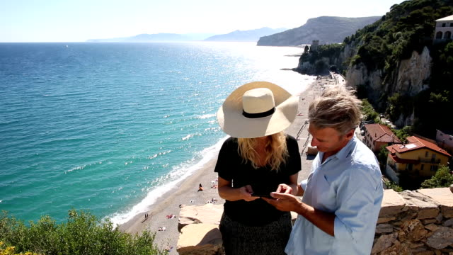 Man takes pic of woman on stone wall above beach