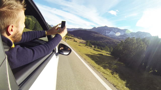 Man takes picture from moving car using digital tablet
