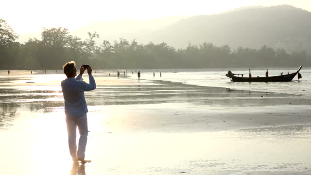 Man takes picture with smart phone, on beach at sunrise