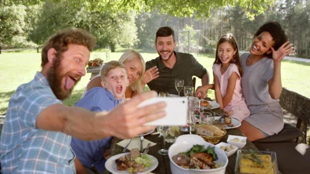 SLO MO Man nemen van een selfie met zijn gezin aan de picknicktafel