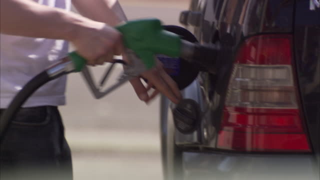 CU Man taking nozzle from gas pump and refueling his SUV, mid section / Pittsburgh, Pennsylvania, USA