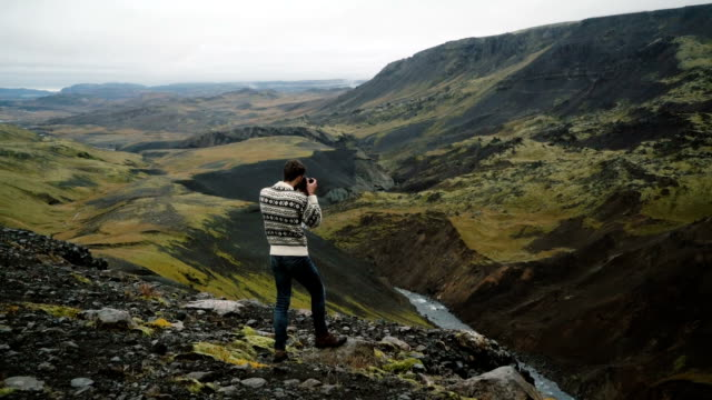 Man taking photo of Haifoss  waterfall valley in mountains